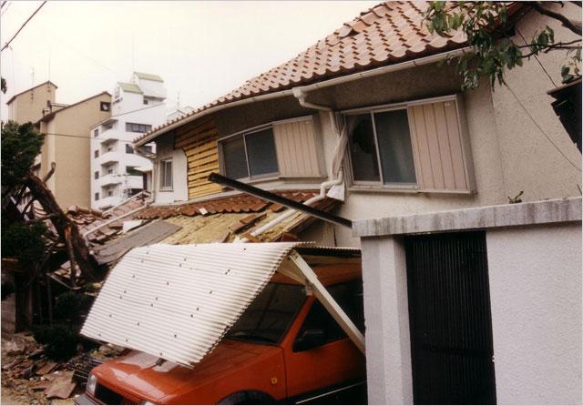 写真1:阪神大震災の2階が重く倒れた家