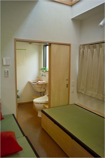 引き戸を開けると畳ベッドからそのまま足を降ろしてベンチ式トイレへ